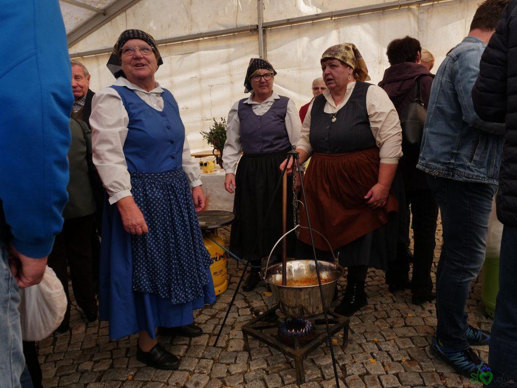 Donne in abiti tradizionali cucinano il Prleški pisker