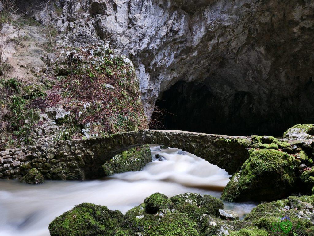 Il pittoresco ponticello in pietra di fronte alla grotta